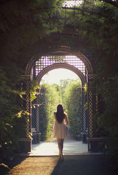 femme marchant sous une pergola naturelle